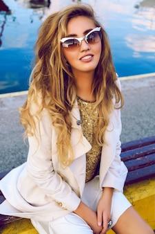 Outdoor-mode-porträt eines schönen modells, das ein warmes, stilvolles outfit mit mantel und turnschuhen trägt, hat stilvolle, gekräuselte, blonde ombre-haare und sitzt im city yacht club. herbst streetstyle.