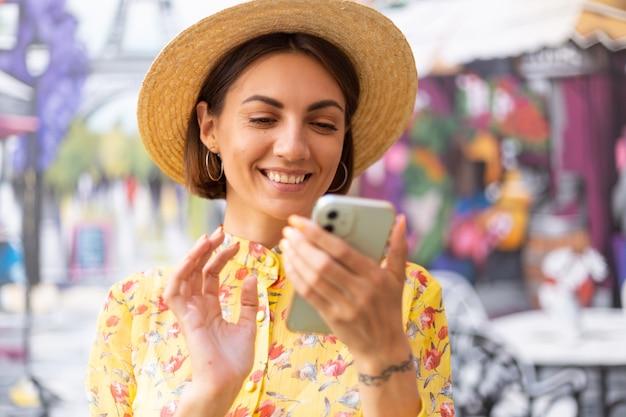 Outdoor-modeporträt der frau im gelben sommerkleid auf der bunten straßenwand