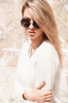 Outdoor-modeporträt der jungen hübschen frau mit runder sonnenbrille
