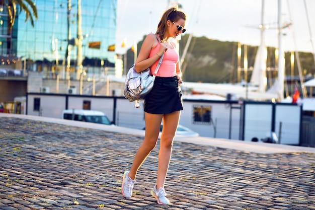 Outdoor-modeporträt der jungen sportlichen frau, die spaßreise und das gehen am luxusyachtclub, abendsonnenlicht, helle farben hat