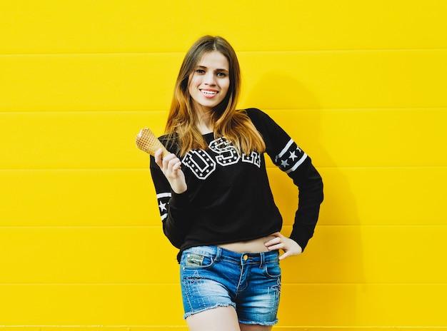 Outdoor-modeporträt des jungen hipster-mädchens mit eiscreme auf gelb