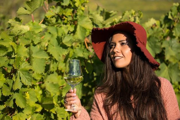 Outdoor-porträt einer wunderschönen jungen frau, die ein glas wein in einem weinberg genießt. weibchen mit staylish-hut im weinberg.