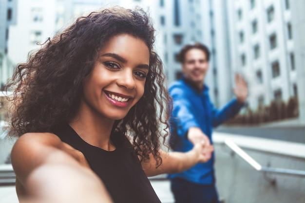 Outdoor-porträt schöne glückliche afroamerikanische frau, die selfie mit ihrem freund macht