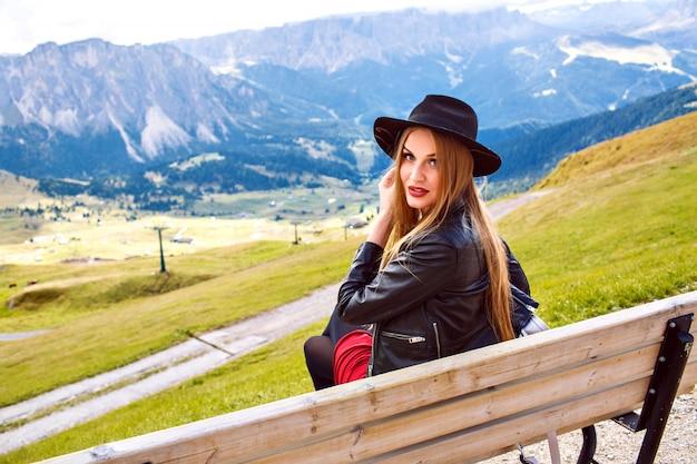 Outdoor-reisebild der stilvollen frau, die in der bank am gebirgsresort sitzt, zeigt durch ihre hand auf erstaunlicher ansicht zu den alpenbergen, luxusreise.