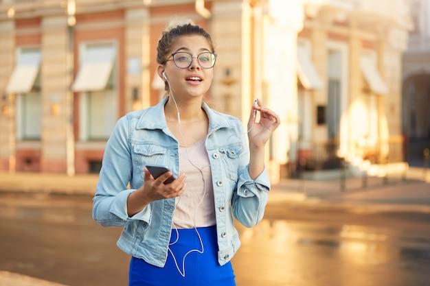 Outdoor-shooting der jungen frau in brille geht lässig gekleidet durch die stadt, hört in kopfhörern lieblingsmusik