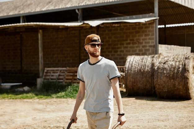 Outdoor-sommeraufnahme des attraktiven jungen mannes mit dicken stoppeln, die auf bauernhof am sonnigen tag arbeiten