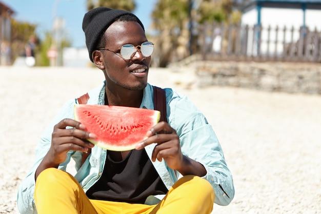 Outdoor-sommeraufnahme des hübschen dunkelhäutigen mannes in den trendigen kleidern und in der brille, die tagsüber am strand entspannen, auf kieselstein mit scheibe saftiger wassermelone sitzen, reife früchte und warmes wetter genießen