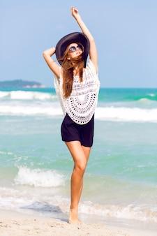 Outdoor-sommermodeporträt der schönen eleganten frau mit perfektem körper und langen beinen, die hut und boho-schickes outfit tragen, posiert am windigen sonnigen tag am tropischen strand, erstaunliche ansicht zum ozean