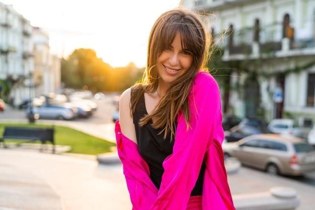 Outdoor-sommerporträt einer gutaussehenden frau in stilvoller rosa jacke.