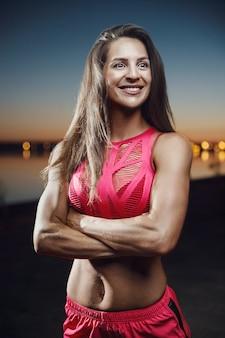 Outdoor-sport schöne starke sexy sportliche muskulöse junge kaukasische fitness frau workout-training im fitnessstudio auf diät auf pump-bauchmuskeln pumpen und posieren, bodybuilding-konzept