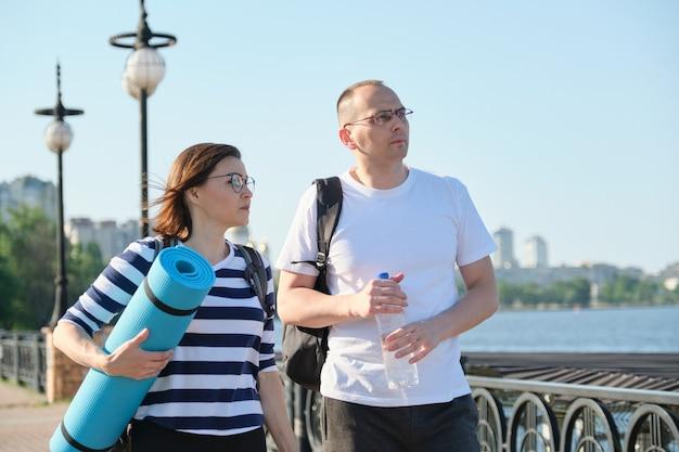 Outdoor walking mann und frau, sprechende menschen, paar mittleren alters in sportbekleidung mit rucksäcken, aktiver gesunder lebensstil und beziehungen von 40-jährigen menschen