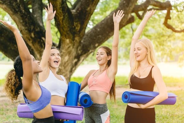 Outdoor yoga klasse, gruppe von jungen gesunden frauen teen glücklich gruß treffen zusammen für übung.