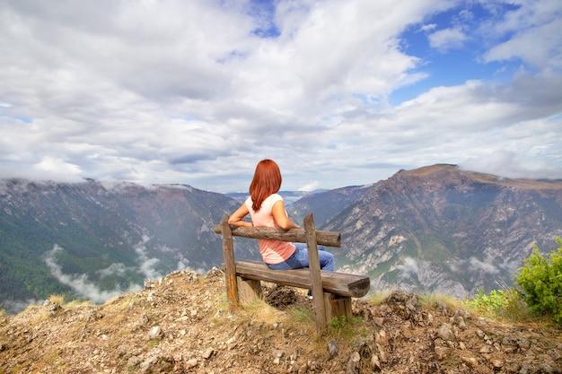 Outfit der lässigen frau. rotes haarmädchen entspannen sich auf der bank, die natur über mountain view-landschaft genießt. travel lifestyle abenteuerurlaub im freien. montenegro