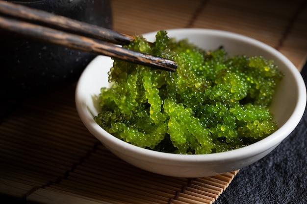 Oval meerestraubenmeerespflanze, abschluss herauf grünen kaviar auf dunklem hintergrund