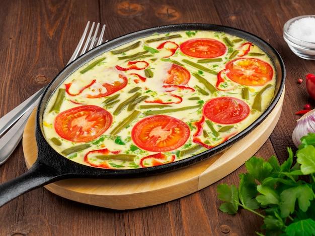 Ovale gusseisenpfanne mit leckerem, heißem omelett mit tomaten. brown-hölzerner beschaffenheitshintergrund