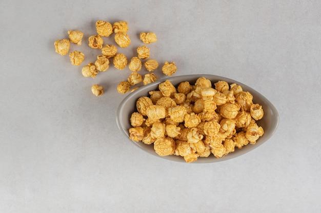 Ovale snackschale gefüllt mit einer portion karamellbeschichtetem popcorn auf marmortisch.