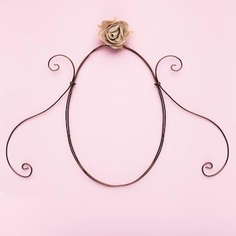 Ovaler formrahmen mit künstlicher rose auf rosa hintergrund