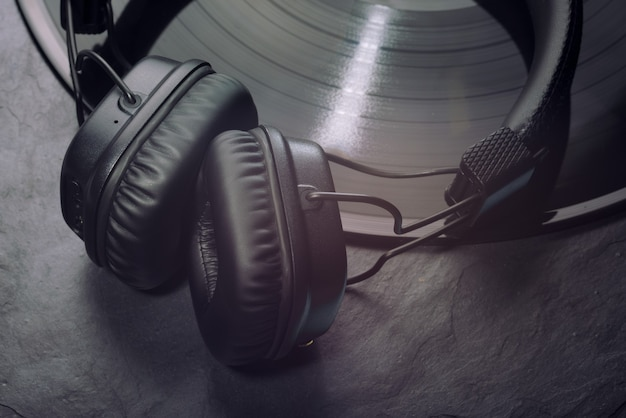 Over- oder on-ear-kopfhörer auf schallplatte. schwarzer hintergrund. nahaufnahme