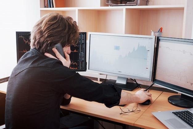 Over-the-shoulder-ansicht von und börsenmakler, die online handeln, während sie bestellungen per telefon annehmen. mehrere computerbildschirme voller diagramme und datenanalysen im hintergrund