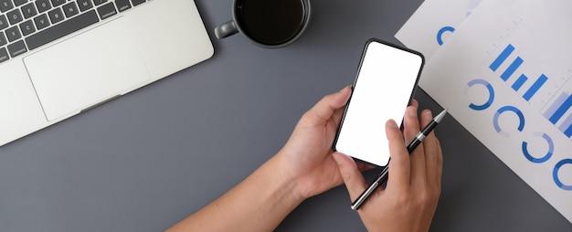 Overhead-aufnahme des geschäftsmannes, der modell-smartphone verwendet, während mit laptop und papierkram gearbeitet wird