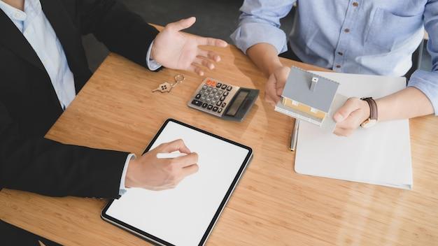 Overhead-aufnahme des house loan agent unter verwendung eines tablets mit leerem bildschirm beim präsentieren für den kunden