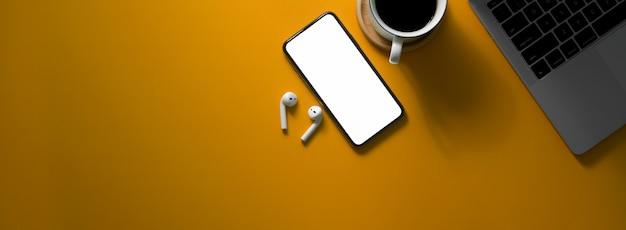 Overhead-aufnahme des kreativen arbeitstisches mit smartphone mit leerem bildschirm, digitalen geräten, kaffeetasse und kopierraum
