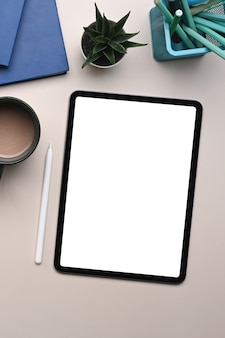 Overhead-aufnahme eines digitalen tablets mit weißem bildschirm, kaffeetasse, briefpapier und notizbuch auf beigem cremefarbenem hintergrund.