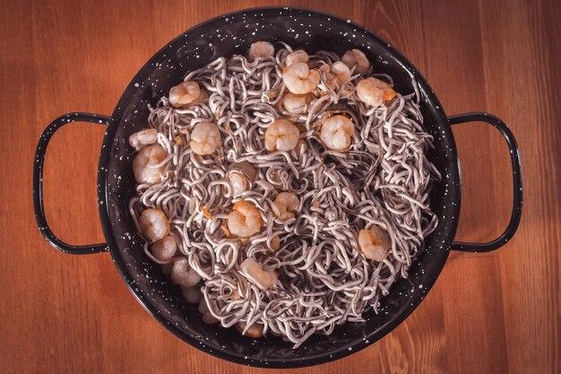 Overhead-aufnahme eines köstlichen tellers aal mit garnelen auf einem holztisch