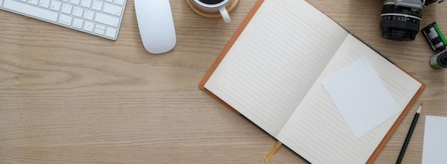 Overhead-aufnahme eines komfortablen arbeitsbereichs mit offenem leerem notizbuch, computergeräten, kamera und kopierbereich
