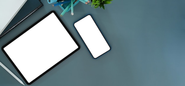 Overhead-aufnahme von digitalem tablet, handy und bürobedarf auf blauem tisch. leerer bildschirm für ihre textnachricht oder informationsinhalte.