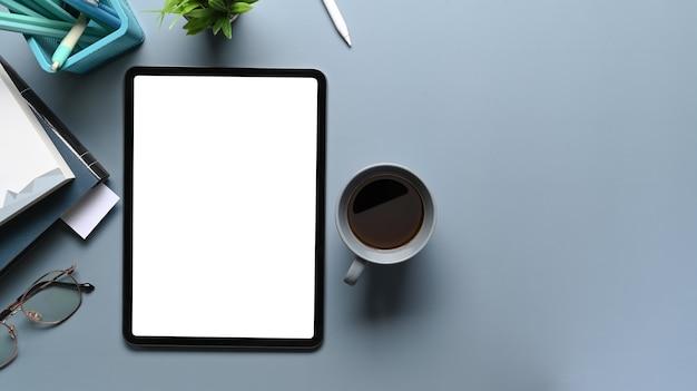 Overhead-aufnahme von mock-up-tablet-computer, kaffeetasse, notebook und schreibwaren auf grauem schreibtisch. leerer bildschirm für die montage der grafikanzeige.