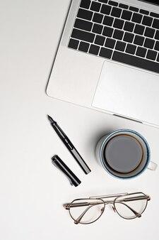 Overhead shot mock-up laptop, kaffeetasse und brillen auf weißem hintergrund.