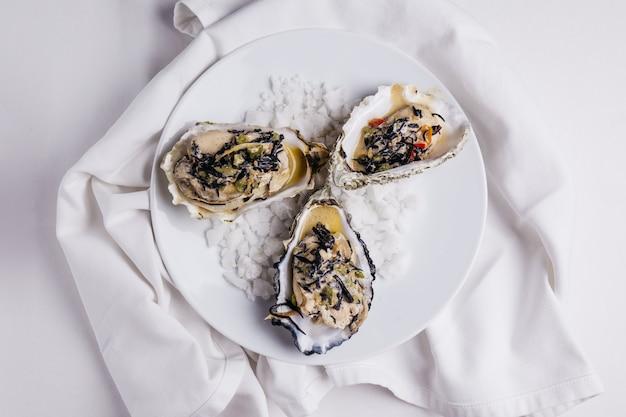Oyster rockefeller und sake-pochierte auster, gekocht in hijki-butter und schwarzem seetang