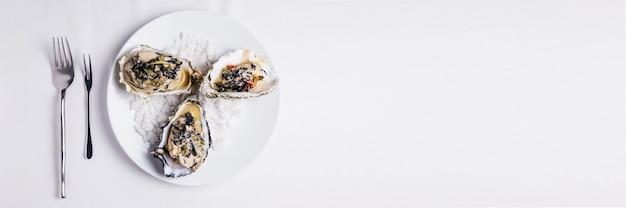 Oyster rockefeller und sake-pochierte auster, gekocht in hijki-butter und schwarzem seetang.