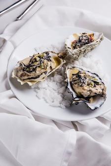 Oyster rockefeller und sake-pochierte auster