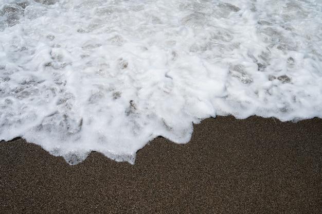 Ozeanwasser, das ans ufer gespült wird. foto in hoher qualität