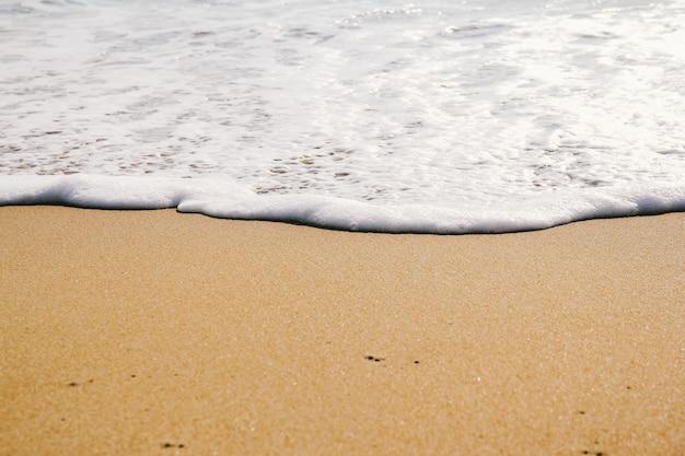 Ozeanwelle auf sandstrandhintergrund