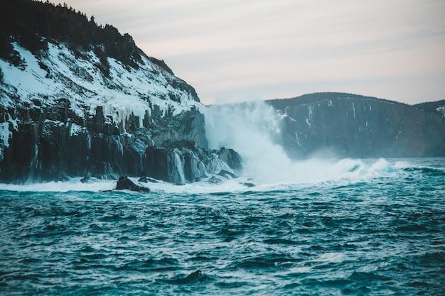 Ozeanwellen, die tagsüber am felsigen ufer abstürzen