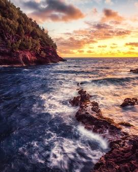 Ozeanwellen, die während des sonnenuntergangs auf felsen abstürzen