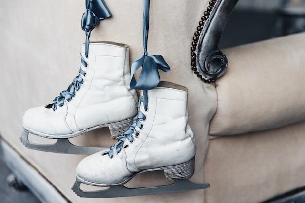 Paar abgenutzte weisse winterlederschlittschuhe zum eiskunstlauf mit schnürsenkeln hängen am band