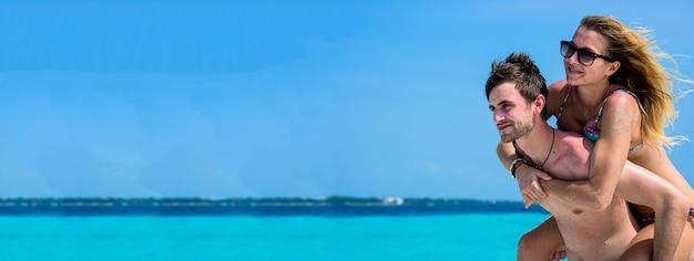 Paar am karibischen strand im urlaub bannerbild mit textfreiraum