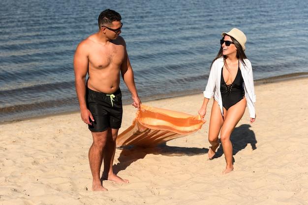 Paar am strand mit luftmatratze
