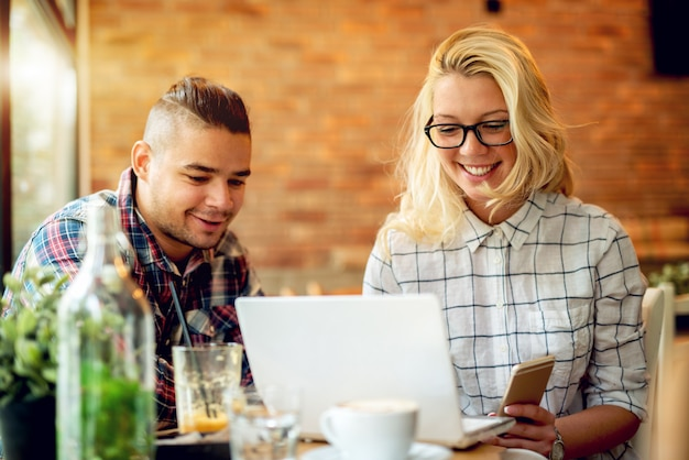 Paar an der café-bar, die smartphones betrachtet.