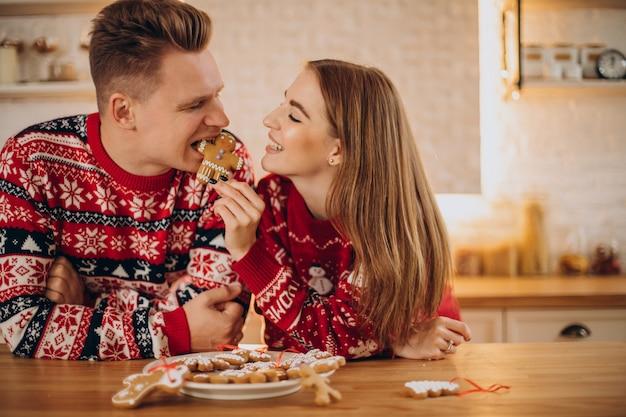 Paar an der küche, die weihnachtsplätzchenmann isst