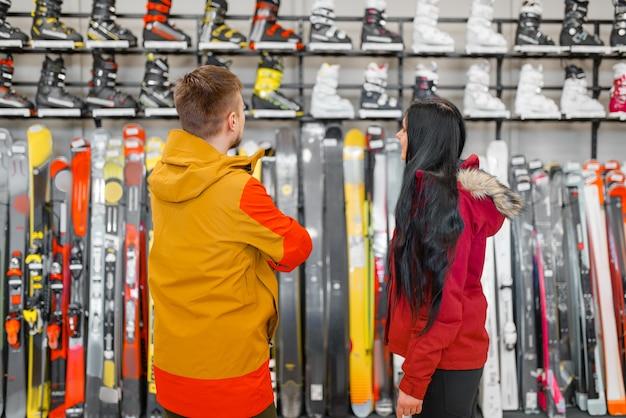 Paar an der vitrine, die ski- oder snowboardausrüstung wählt und im sportgeschäft einkauft.
