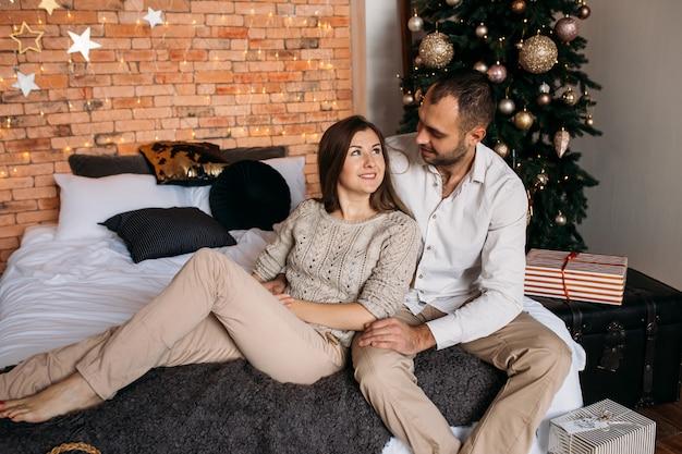 Paar an weihnachten zu hause auf dem bett in der nähe