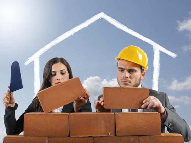 Paar arbeitet wie maurer, um ein haus zu bauen, um eine familie zu haben