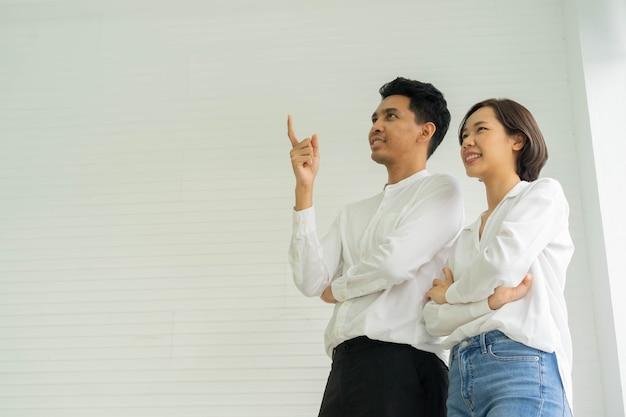 Paar asiatischer liebhaber über weißer wand innerhalb des neuen hauses