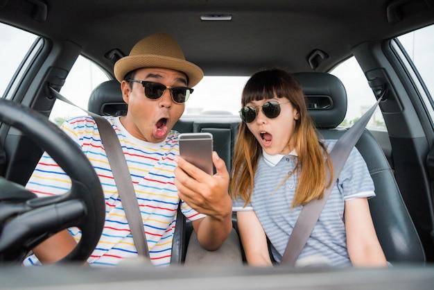 Paar asiatischer mann und frau, die im auto sitzen und telefon betrachten. reisekonzept.