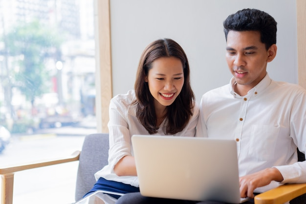 Paar auf couchsofa sitzen und zusammen auf laptop im wohnzimmer in der freizeit am wochenende spielen